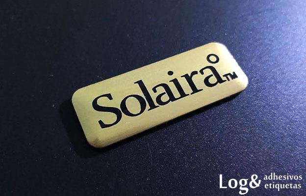 Logotipo metálico con fondo fotoanodizado oro