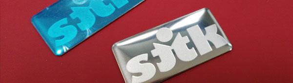 Logo adhesivo metálico en acero inoxidable grabación en bajo relieve. Alto relieve reservado acabado en brillo.