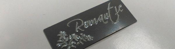 Logos de aluminio embutidos con relieve. Impresión por serigrafía. Corte y embutición con troquel de matricería de dos fases.