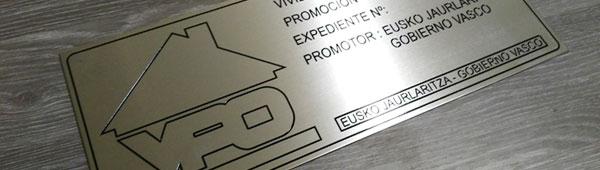 Placa metálica de acero inoxidable grabada en bajo relieve y entintada en negro. Acabado natural